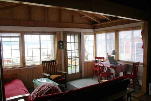 The front porch is surrounded by windows and faces the beach.  Futons fold down for sleeping